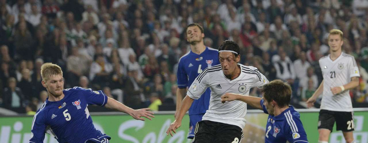 Germany's Mesut Oezil (C) scores his second goal against Odmar Faero (L) and Jonas Naes (2nd R) of Faroe Islands during their 2014 World Cup qualifying soccer match in Hanover, September 7, 2012.  REUTERS/Fabian Bimmer (GERMANY - Tags: SPORT SOCCER)