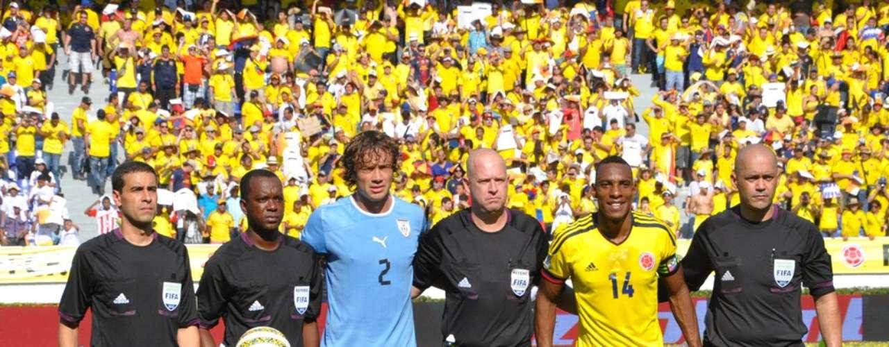 Diego Lugano y Amaranto Perea, capitanes de Uruguay y Colombia respectivamente, con los árbitros del encuentro.