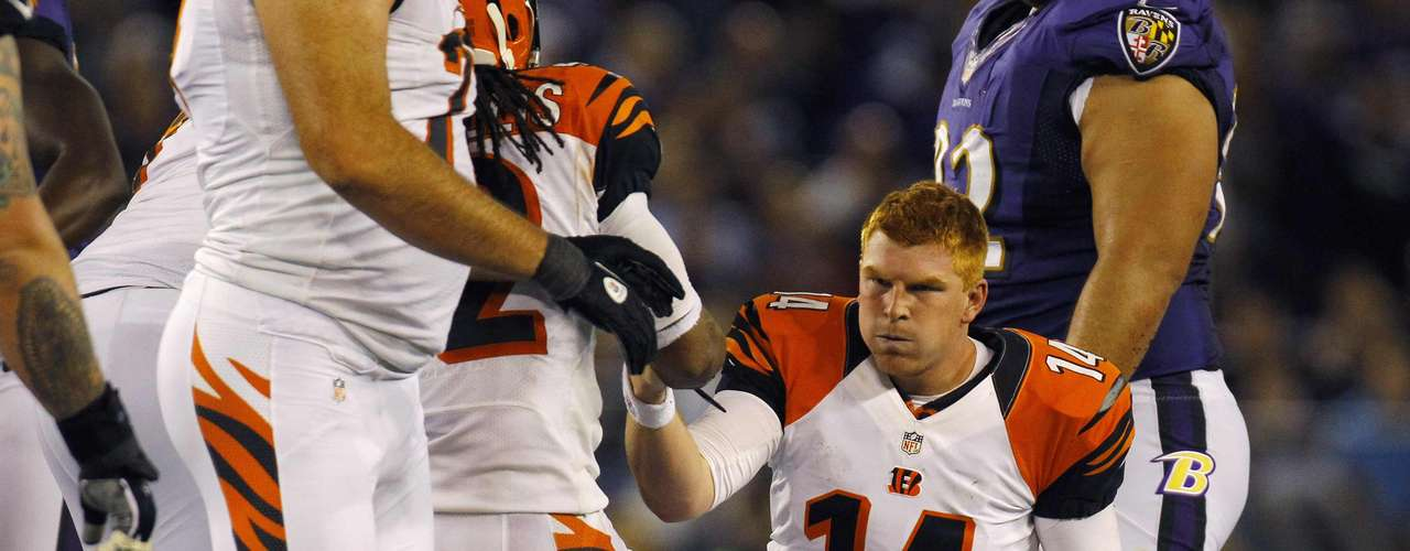 Cincinnati Bengals quarterback Andy Dalton (14) is helped up by a teammate after being tackled and then fumbling the ball against the Baltimore Ravens during the second half of their NFL football game in Baltimore September 10, 2012.
