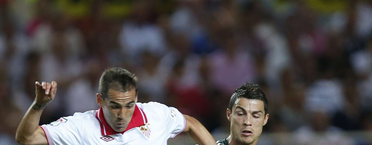 Real Madrid's Cristiano Ronaldo (R) and Sevilla's Fernando Navarro battle for the ball during their Spanish First Division soccer match at Ramon Sanchez Pizjuan stadium in Seville September 15, 2012. REUTERS/Marcelo del Pozo (SPAIN - Tags: SPORT SOCCER)