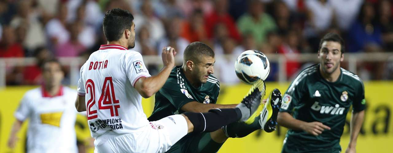 Real Madrid's Karim Benzema (C) is challenged by Sevilla's Tomas Alberto Botia during their Spanish First Division soccer match at Ramon Sanchez Pizjuan stadium in Seville September 15, 2012. REUTERS/Marcelo del Pozo (SPAIN - Tags: SPORT SOCCER)