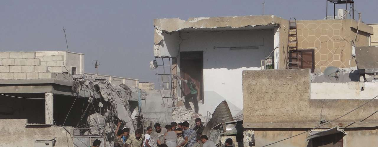 Residents and members of the Free Syrian Army search for bodies under rubble of a house, which was destroyed after being shelled by a MIG airstrike in the northern town of Saraqib, near Idlib  September 15, 2012.