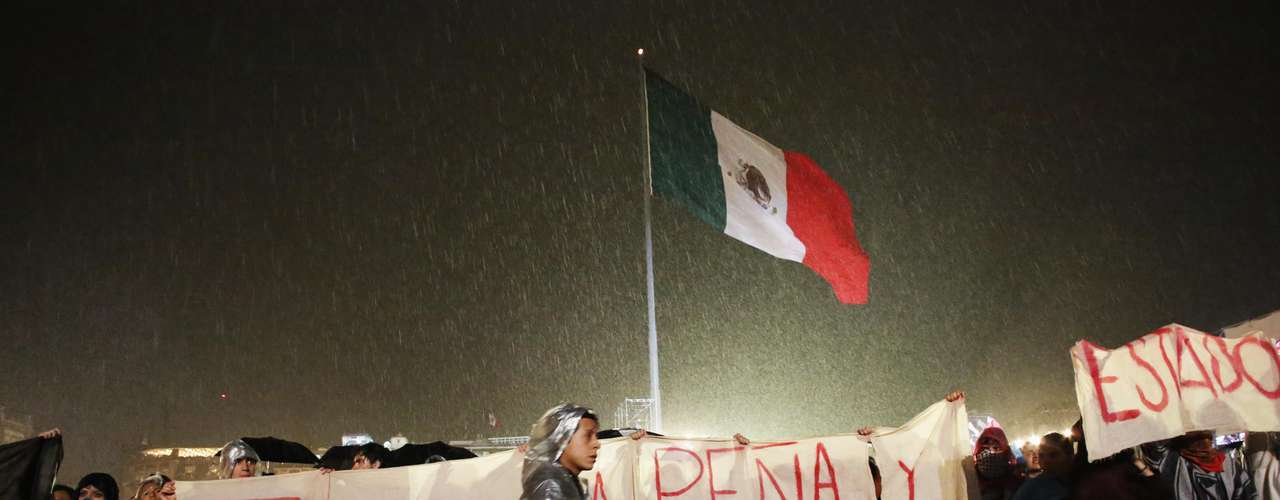 Protesters hold a banner as they protest against Mexican President Felipe Calderon and Mexico's President-elect Enrique Pena Nieto, as other Mexicans celebrate the 202nd anniversary of their independence from Spain at the Zocalo Square in downtown Mexico City September 15, 2012. President Calderon shouted the \