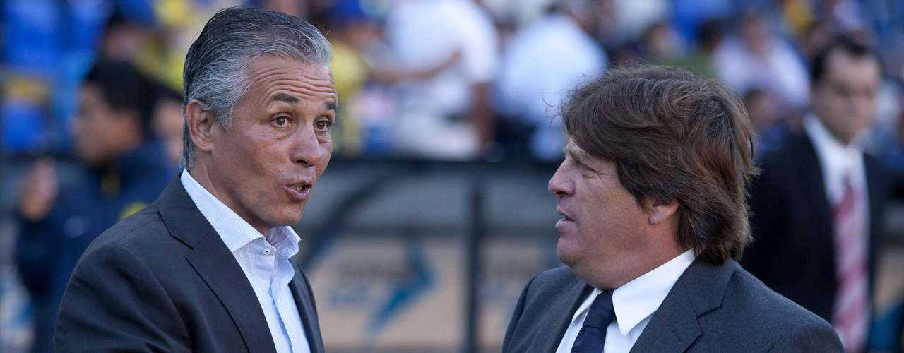 Managers Sergio Bueno and Miguel Herrera shake hands before the start of the match.