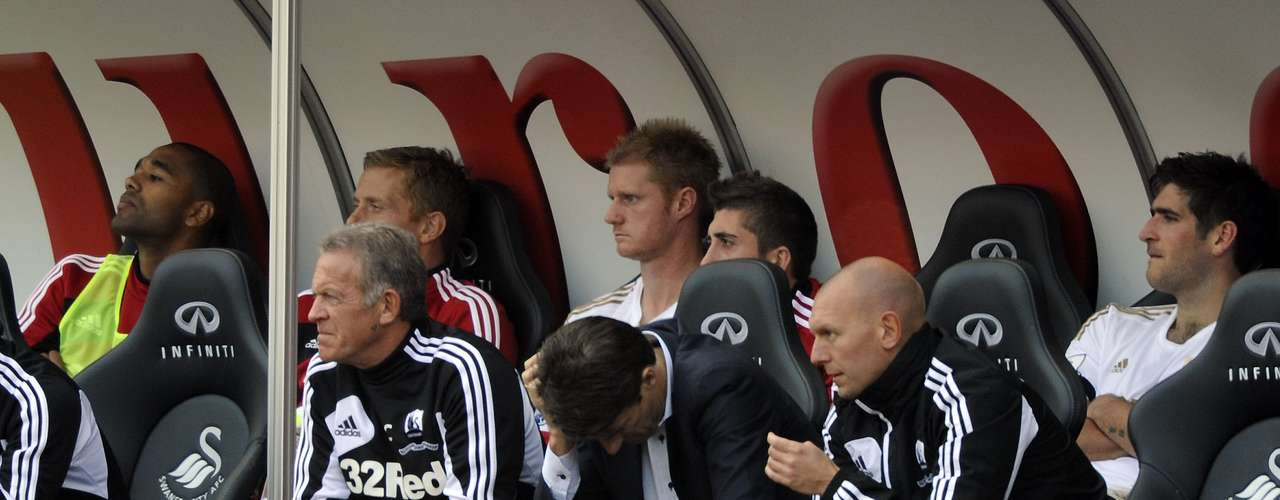 Swansea City's manager Michael Laudrup (front row 2nd R) sits in the team dugout.