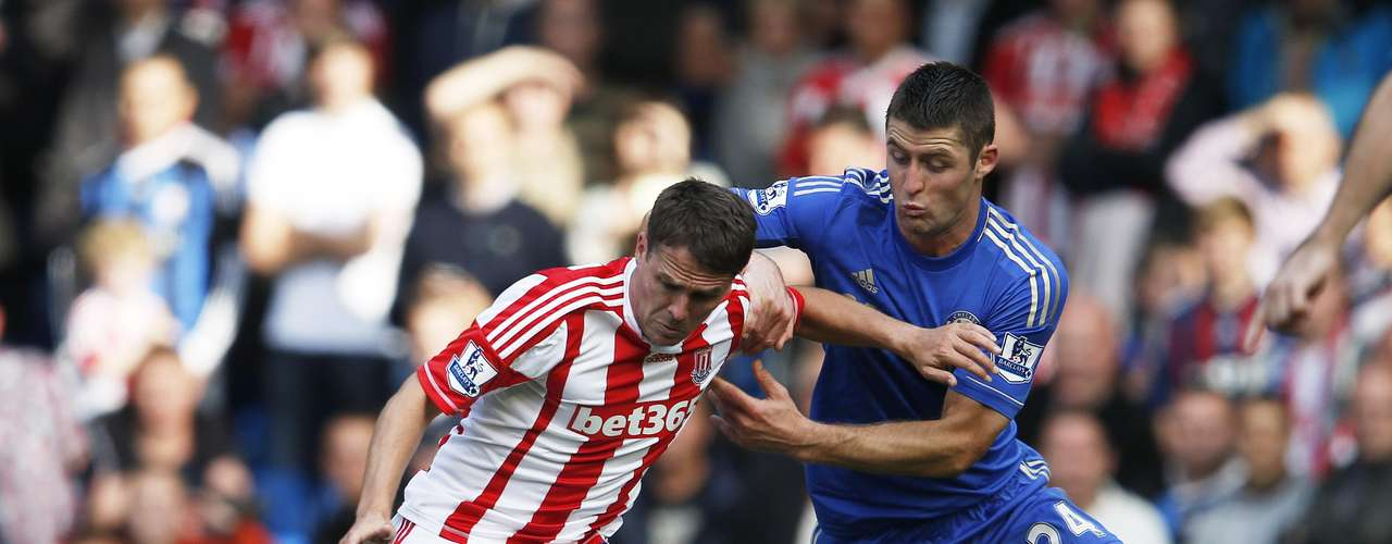 Chelsea's Gary Cahill challenges Stoke City's Michael Owen during their English Premier league soccer match.