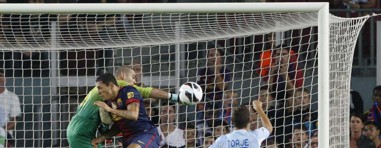 Barcelona's goalkeeper Victor Valdes (L) blocks the ball, as he crashes into team mate Adriano (C), next to Granada's Gabriel Torje.    REUTERS/Albert Gea