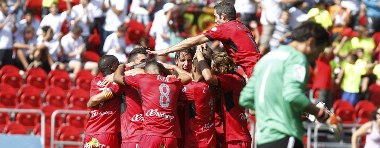Mallorca's players celebrate Victor Casadesus' goal against Valencia as Valencia's goalkeeper Diego Alves (R) reacts during their Spanish First division soccer match at Iberostar stadium in Palma de Mallorca, September 23, 2012.