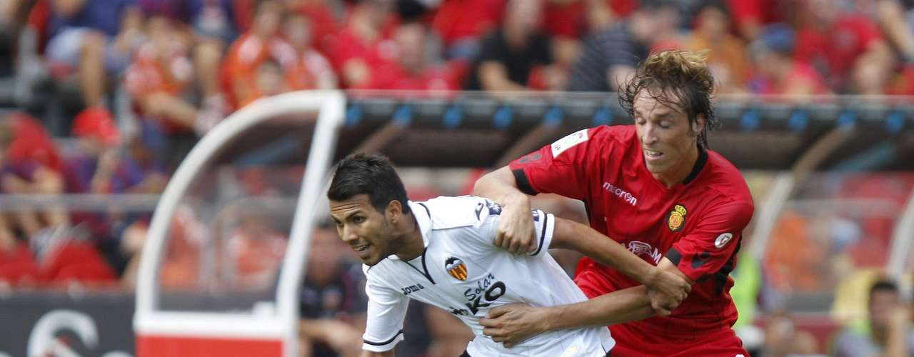Mallorca's Tomas Pina (R) challenges Valencia's Jonathan Viera during their Spanish First division soccer match at Iberostar stadium in Palma de Mallorca, September 23, 2012.