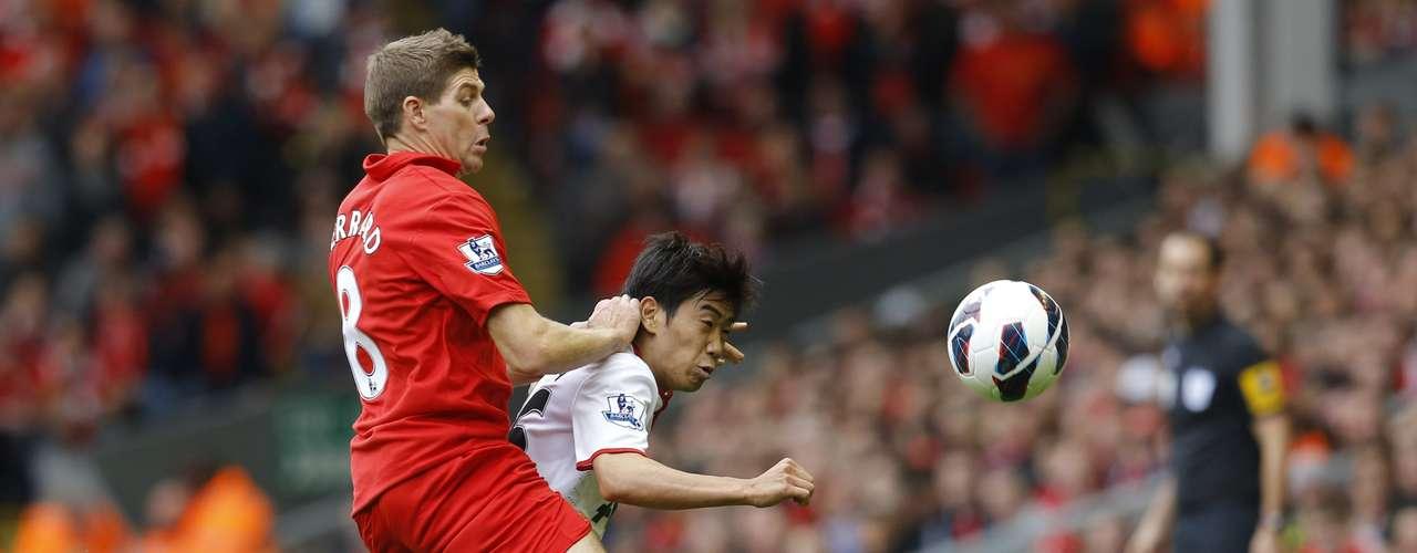 Steven Gerrard (L) challenges Manchester United's Shinji Kagawa.