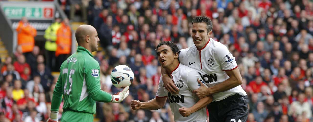 Manchester United's Rafael (C) celebrates his goal with teammate Robin Van Persie (R) as Liverpool's goalkeeper Pepe Reina walks past;