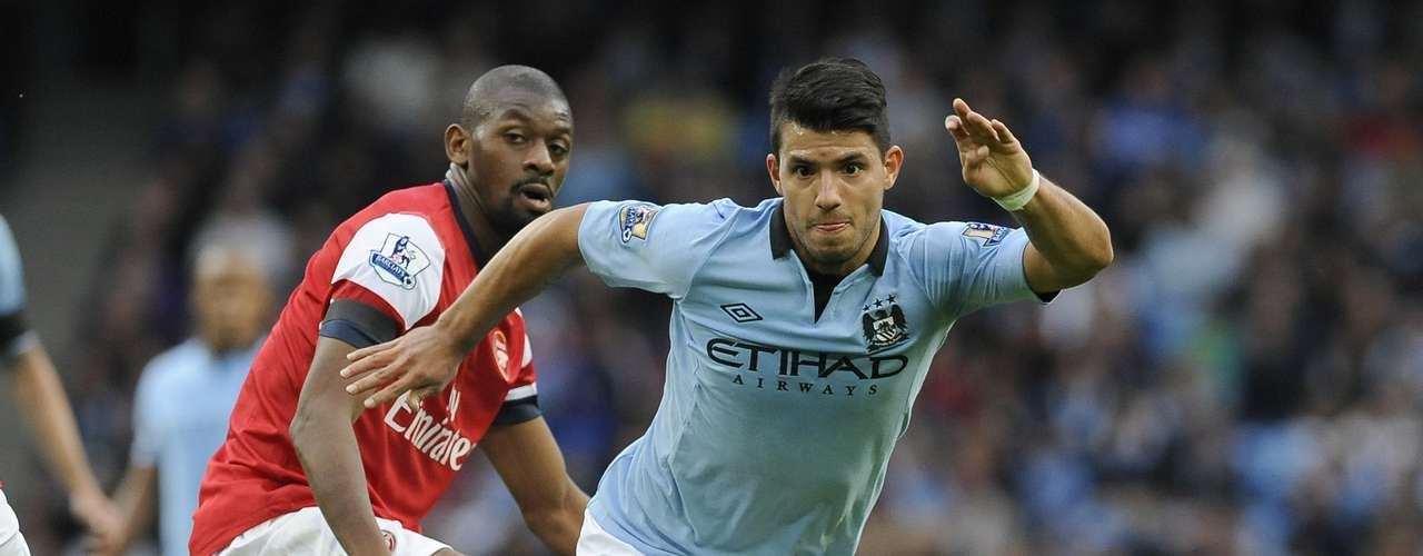 Sergio Aguero (R) runs past Arsenal's Abou Diaby.