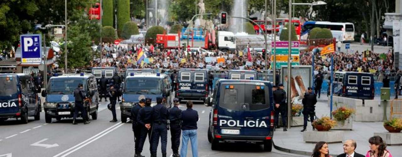 Furgones policiales cerrando la manifestación. En primer plano, tres personas de boda
