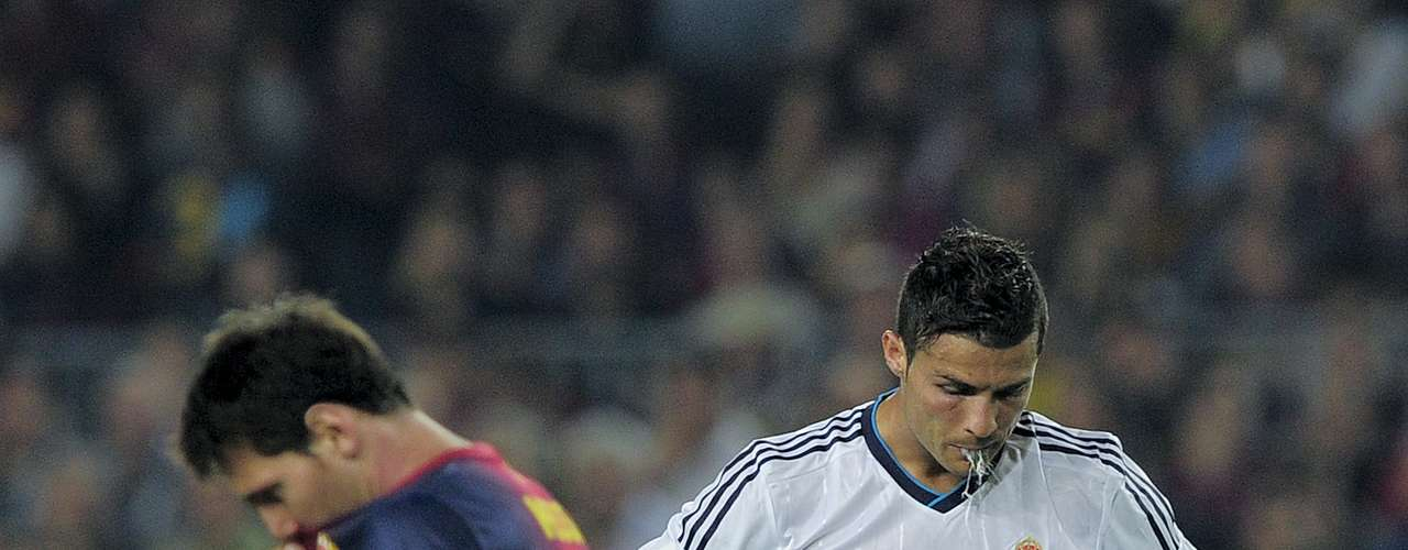 Ronaldo spits on the ground as Messi walks past him in the foreground, both players looking tense as the match reached its climax.
