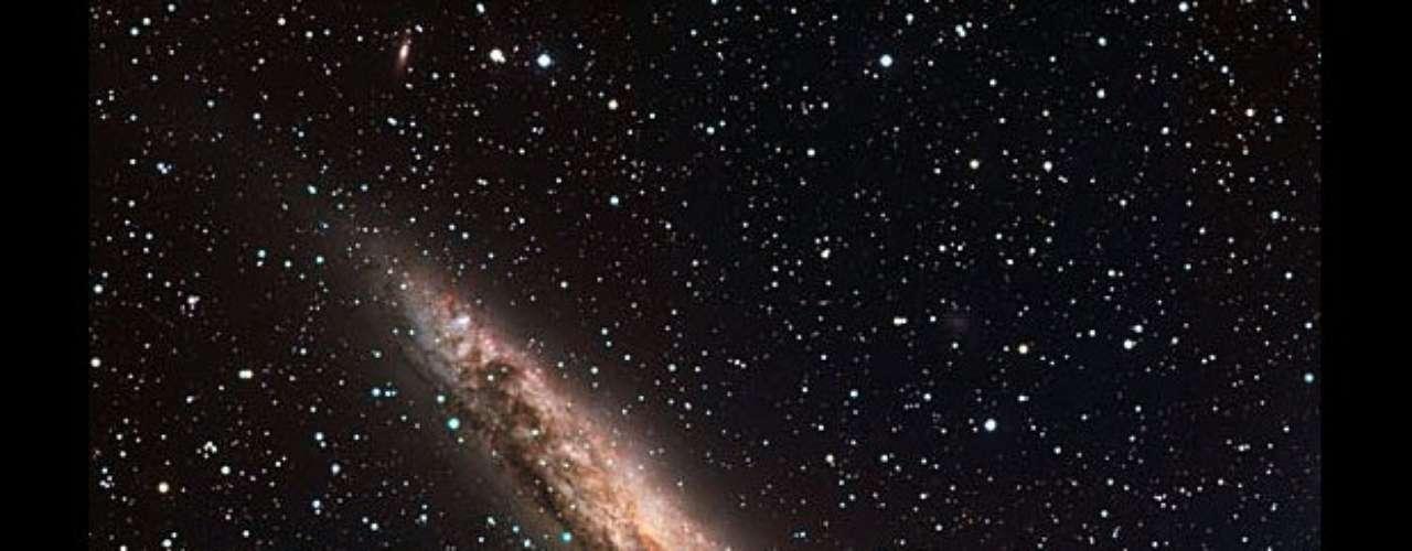 Las observaciones de esta galaxia, NGC 4945, indican que es bastante parecida a la Vía Láctea por sus luminosos brazos en espiral y el centro con forma de barra. La parte color rosa claro es donde nacen las estrellas. En el centro probablemente se encuentra un enorme agujero negro. La NGC 4945 es la constelación del Centauro y se encuentra a 13 millones años luz.