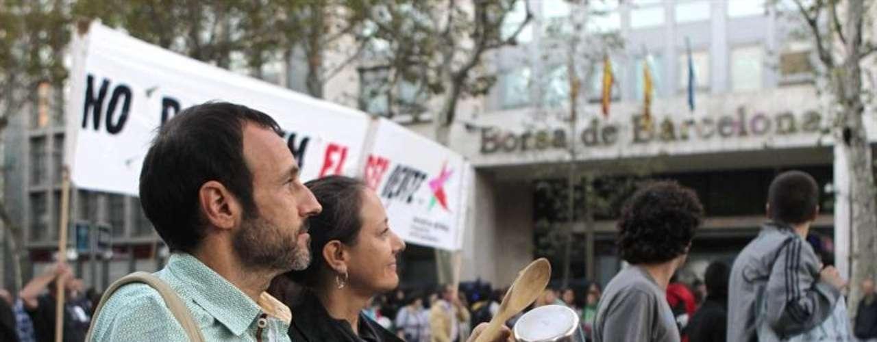Varias personas a su paso por la sede de la bolsa de Barcelona durante la manifestación de acción global convocada por el colectivo 15-M de Barcelona, en protesta por las deudas de los bancos.