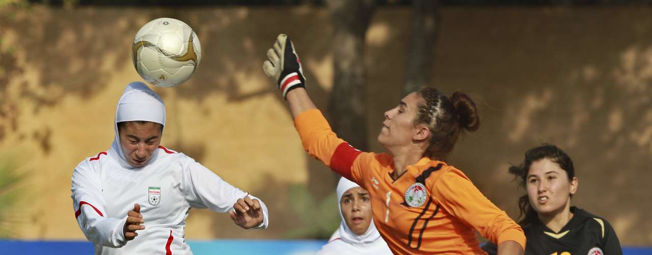 Iran's Seyedeh Naraghi (L) fights for the ball with Tajikistan's goalkeeper Rakhmonova Saida (2nd R) during their AFC U-19 Women's Championship qualifying soccer match at Petra Stadium in Amman October 18, 2012. Iranian women had been banned from participating in many international matches because of the hijabs (covered uniforms) but a recent ruling by the Asian Football Confederation (AFC) allowed them to be used. REUTERS/Muhammad Hamed