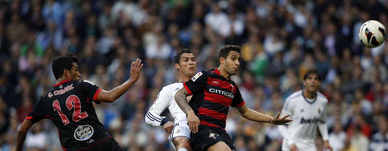Real Madrid's Cristiano Ronaldo (2nd L) kicks the ball past Celta Vigo's Gustavo Daniel Cabral (L) and Hugo Mallo during their Spanish First Division soccer match at Santiago Bernabeu stadium in Madrid October 20, 2012. REUTERS/Susana Vera (SPAIN - Tags: SPORT SOCCER)