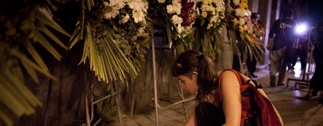 Una mujer coloca una vela afuera del Congreso nacional el lunes 5 de noviembre del 2012 en Buenos Aires, Argentina, donde los restos del cantante y cineasta Leonardo Favio eran velados. (AP Foto/Víctor R. Caivano)