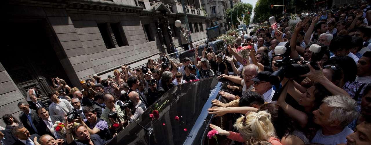 Admiradores tocan la carroza fúnebre que traslada a un cementerio los restos del cantante y cineasta argentino Leonardo Favio, el martes 6 de noviembre del 2012 en Buenos Aires. Favio falleció el lunes. (AP Foto/Víctor R. Caivano)