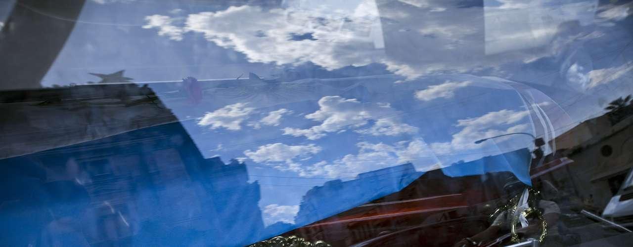El cielo se refleja en una ventana de la carroza fúnebre que traslada los restos del cantante y cineasta argentino Leonardo Favio a un cementerio, el martes 6 de noviembre del 2012 en Buenos Aires. Favio falleció el lunes. (AP Foto/Víctor R. Caivano)