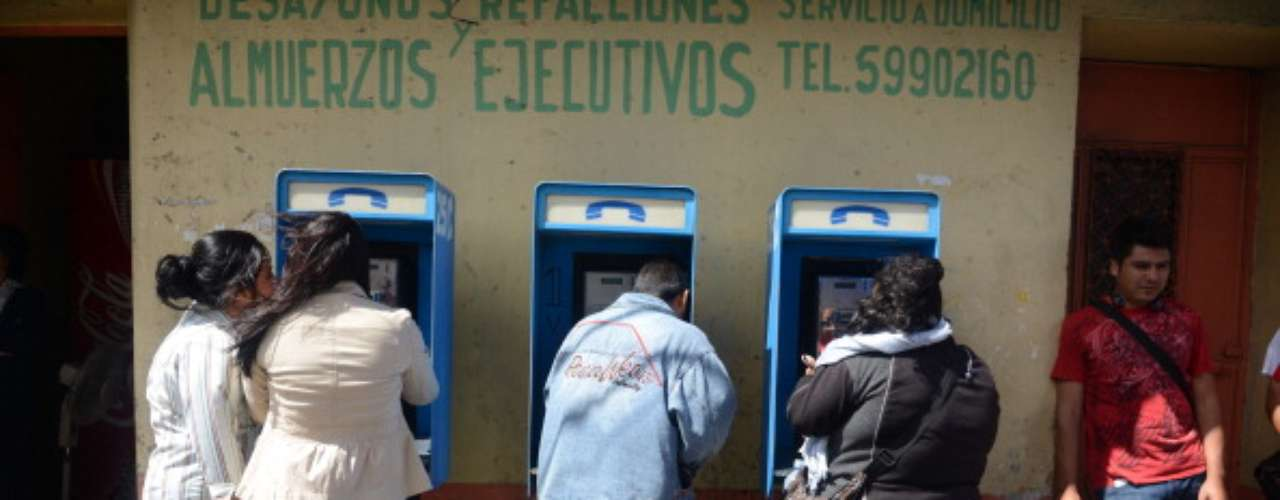 Guatemalans rush to the public phones to check on their family members.