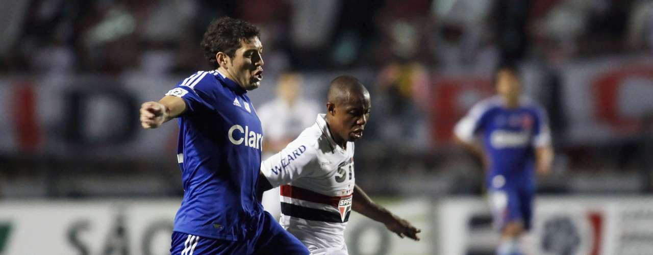 Jose Rojas of Chile's Universidad de Chile fights for the ball with Wellington (R).