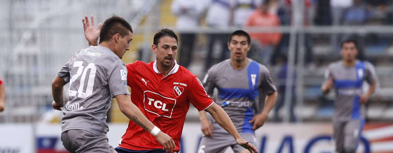 Kevin Harbottle (L) of Chile's Universidad Catolica fights for the ball with Jonathan Santana.