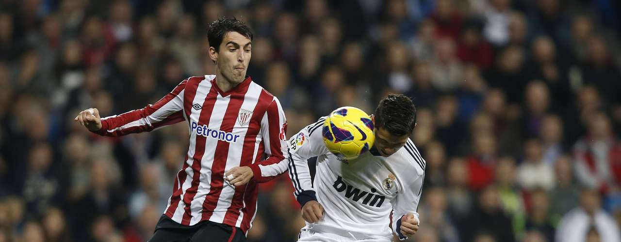 Real Madrid's Cristiano Ronaldo (R) heads the ball past Athletic Bilbao's Andoni Iraola