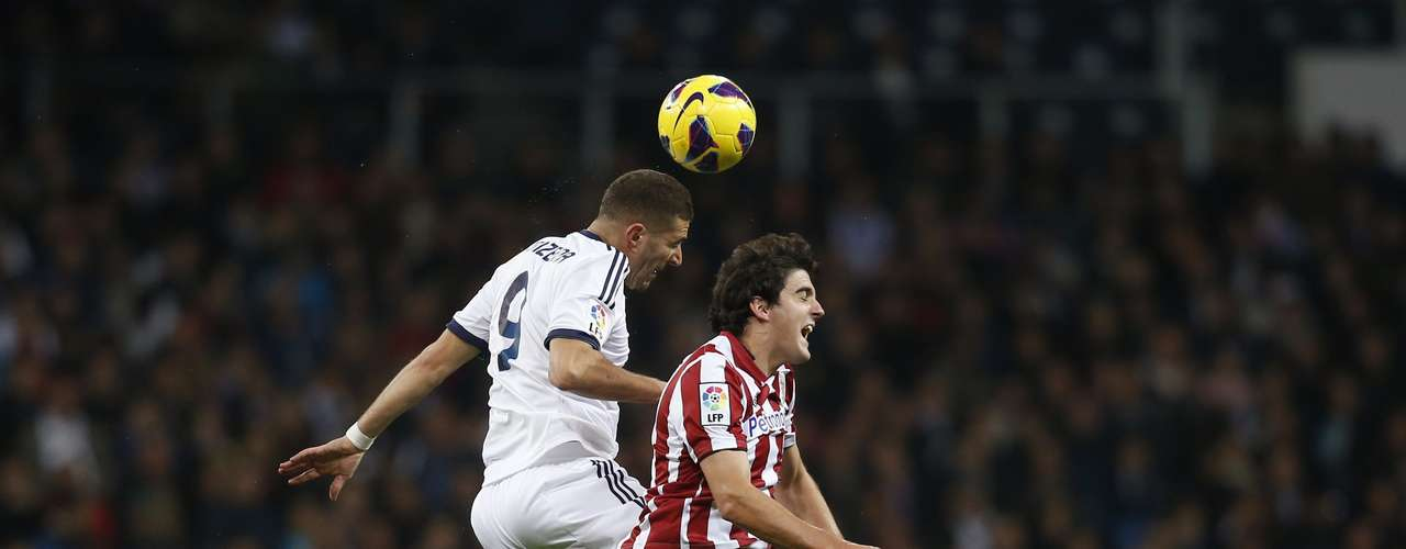 Real Madrid's Karim Benzema (L) fights to head the ball with Athletic Bilbao's Mikel San Jose.