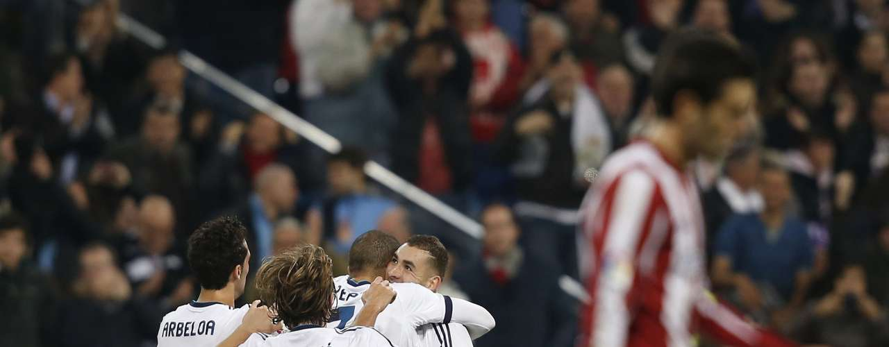 Real Madrid's Karim Benzema (R) is congratulated by teammates on his second goal.
