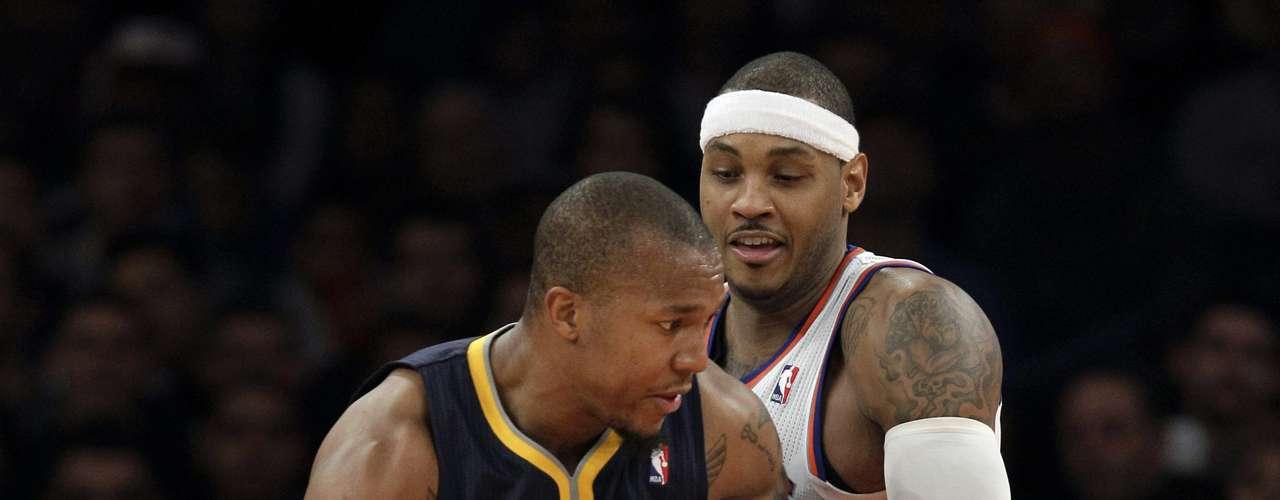 Carmelo Anthony, de los Knicks, defiende ante el ataque de David West, de los Pacers.