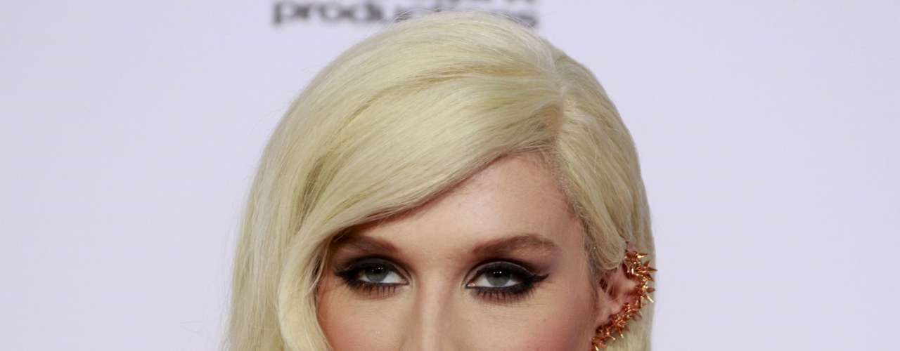 Singer Kesha displays her jewelry as she arrives at the 40th American Music Awards in Los Angeles, California, November 18, 2012.