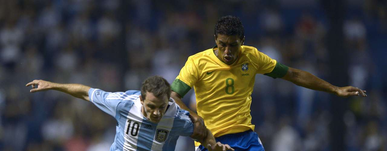 Argentina's midfielder Walter Montillo (L) vies for the ball with Paulinho.