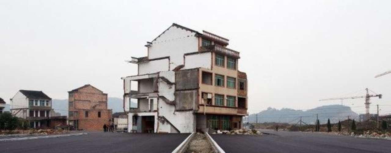 10- La casa que resiste en mitad de una carretera. Conozca la que probablemente es la casa con la peor ubicación de China pero con los mejores accesos. Pertenece a una pareja de la ciudad de Wenling, en el sudeste del país, que se niega a dejar su edificio a pesar de que han construido una autopista a su alrededor. (Fuente: BBC Mundo)