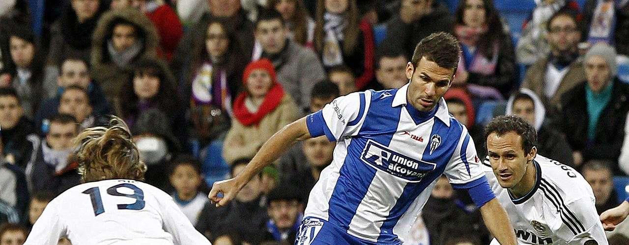 El delantero del Alcoyano David Torres controla el balón ante los jugadores del Real Madrid, el croata Luka Modric y el portugués Ricardo Carvalho