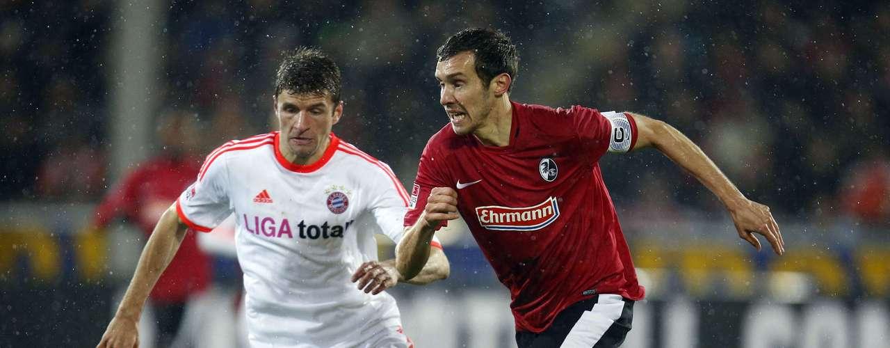 Bayern Munich's Thomas Mueller (L) challenges SC Freiburg's Julian Schuster.