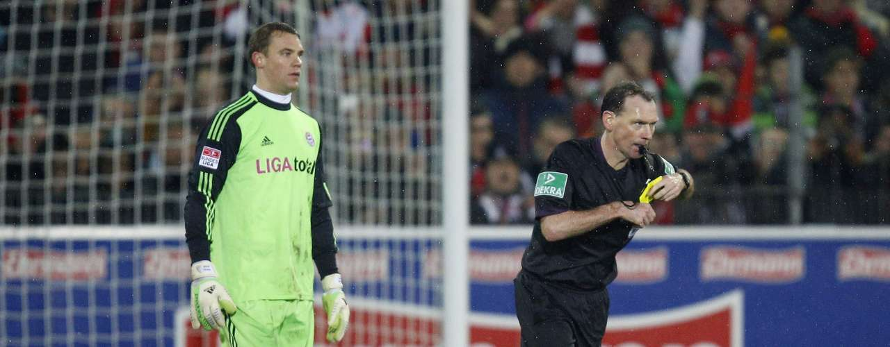 Bayern Munich's goalkeeper Manuel Neuer (L) receives the yellow card from referee Florian Meyer.