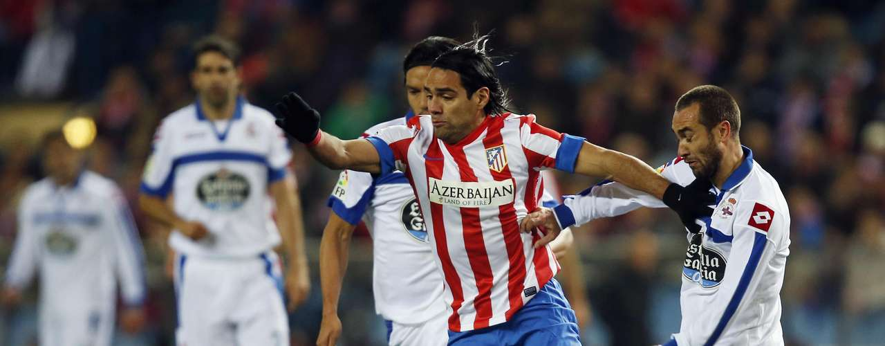 Radamel Falcao (C) fights for the ball with Deportivo La Coruna's Abel Aguilar (L) to scored his second goal of the night.