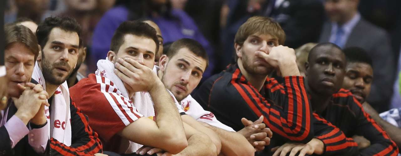 Toronto Raptors' Jose Calderon of Spain (L), Linas Kleiza of Lithuania (2nd L) and Jonas Valanciunas of Lithuania (3rd L), sit on the bench during the final minutes of their game against the Los Angeles Clippers during their NBA basketball game in Los Angeles, California, December 9, 2012.