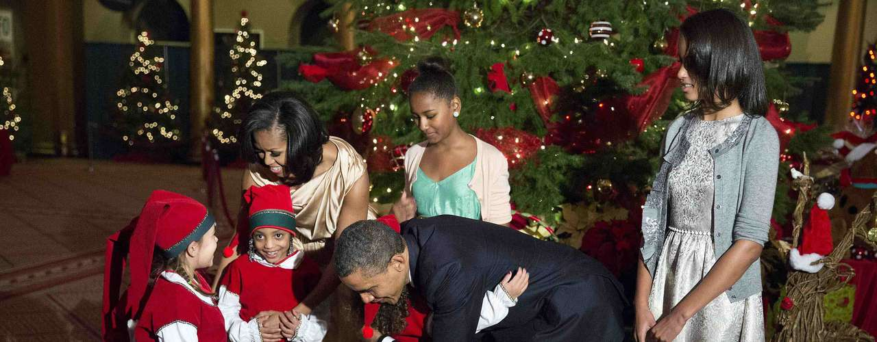 REFILE - CORRECTING POSITION OF SASHA OBAMA U.S. President Barack Obama greets children dressed as Christmas elves as First Lady Michelle Obama and their daughters Sasha (2nd L, back) and Malia watch during Christmas in Washington concert at the National Building Museum in Washington December 9, 2012. Korean rapper Psy is expected to perform along with Diana Ross, Demi Lovato, Megan Hilty, Scott McCreery, and Chris Mann. REUTERS/Joshua Roberts (UNITED STATES - Tags: POLITICS ENTERTAINMENT SOCIETY)