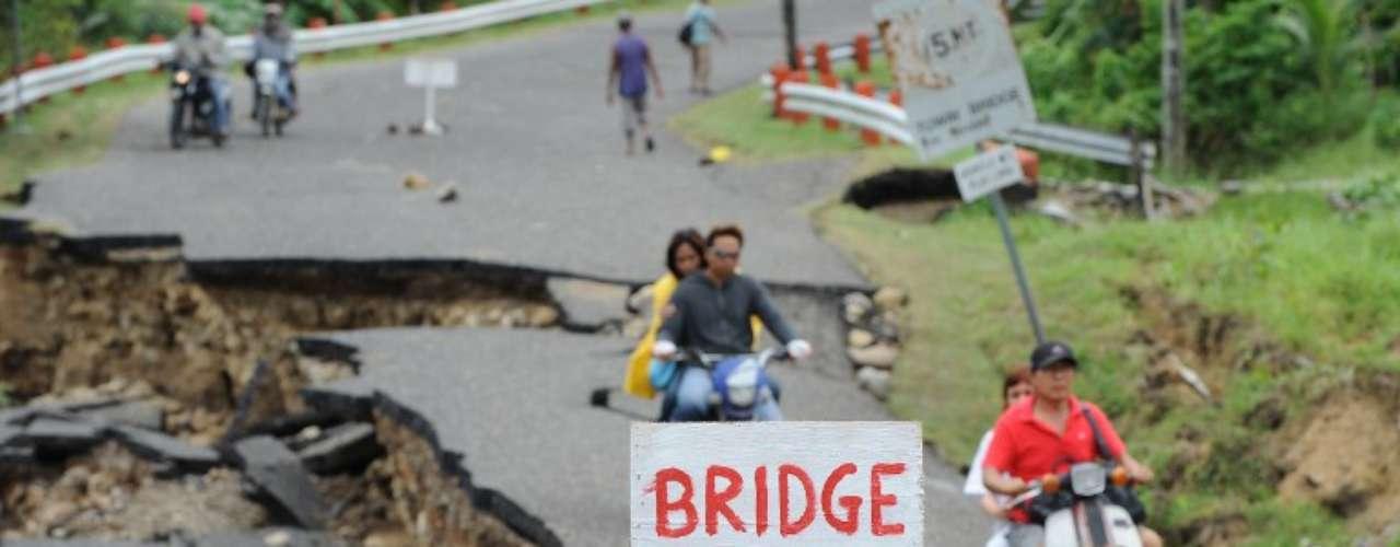 Conductores pasan por una carretera damnificada por un terremoto enGuihulngan, Filipinas.