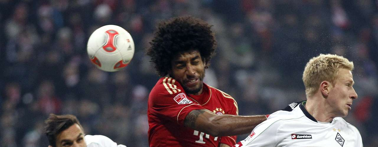 Bayern Munich's Dante (C) fights for the ball with Borussia Monchengladbach's Mike Hanke (R) and Martin Stranzl. REUTERS/Dominic Ebenbichler
