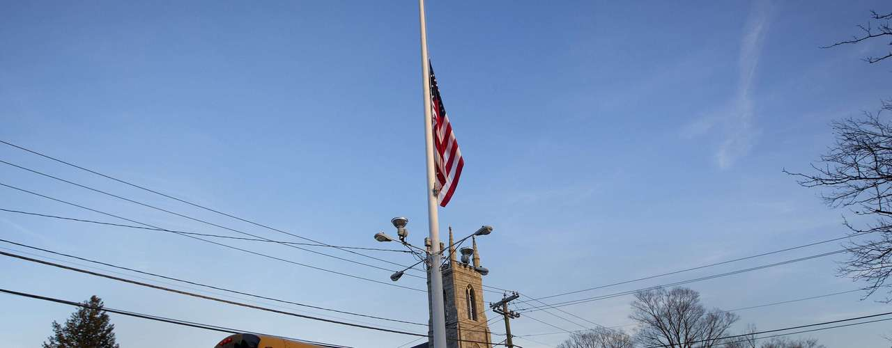 A flag is seen at half mast as a school bus passes along Main Street in Newtown, Connecticut December 14, 2012. A heavily armed gunman opened fire on school children and staff at a Connecticut elementary school on Friday, killing at least 26 people, including 18 children, in the latest in a series of shooting rampages that have tormented the United States this year. REUTERS/Shannon Stapleton (UNITED STATES - Tags: CRIME LAW EDUCATION)