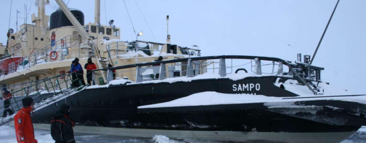 En la imagen unos turistas se bañan en las gélidas aguas del norte de Laponia participando en una excursión a bordo del rompehielos Sampo.