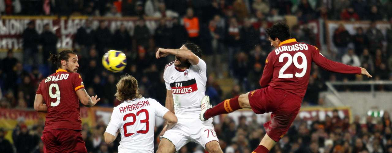 AS Roma's Nicolas Burdisso (R) heads the ball to score against AC Milan.
