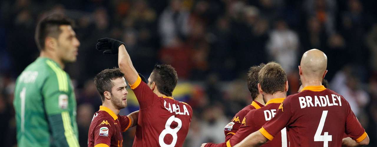 AS Roma's Erik Lamela (8) celebrates with his teammates after scoring as AC Milan's goalkeeper Marco Amelia (L) watches.