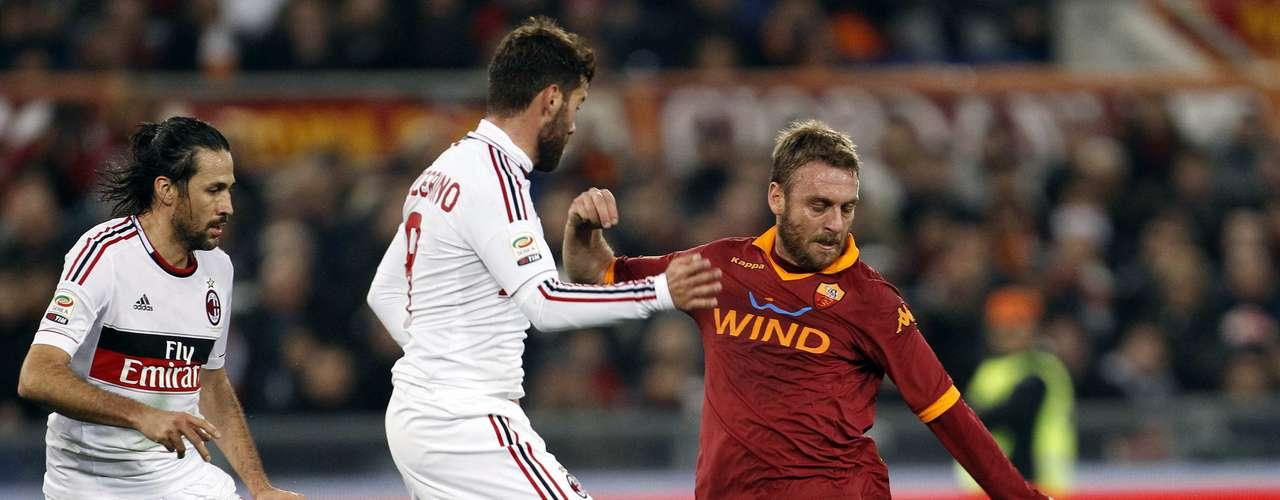 AC Milan's Mario Yepes (L) and Antonio Nocerino (C) challenge AS Roma's Daniele De Rossi.