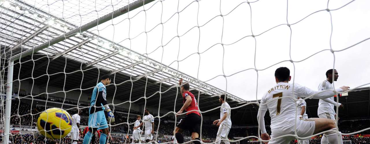 Swansea City's Leon Britton (R) fails to stop Manchester United's Patrice Evra (obscured) from scoring a goal.