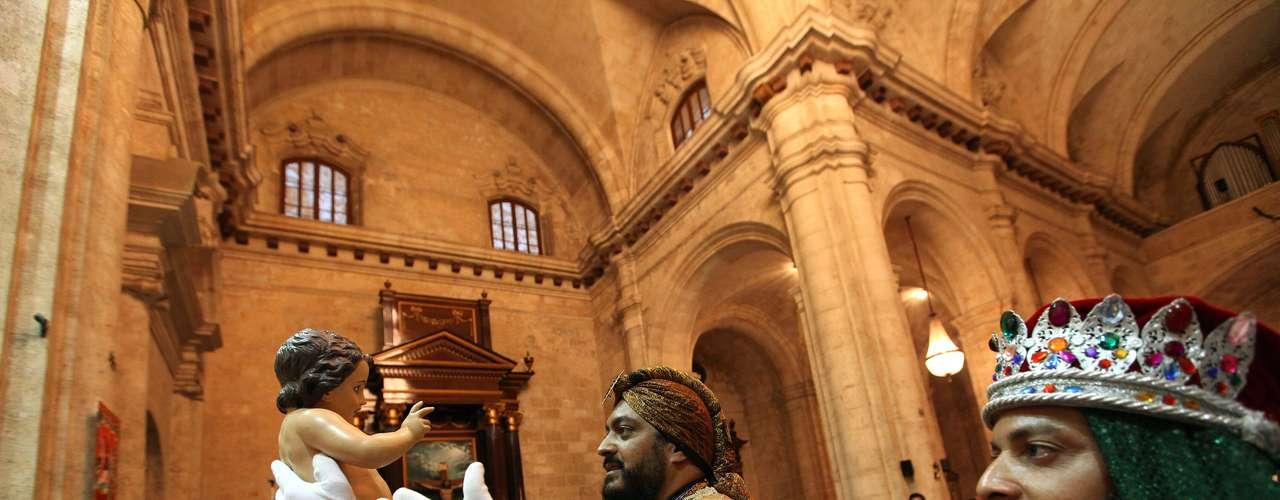 Hombres disfrazados de Reyes Magos sostienen una imagen del Niño Jesús durante una ceremonia para celebrar la epifanía en la Catedral de La Habana, Cuba.